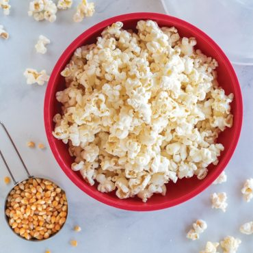Top view of bowl with popcorn, cup with popcorn kernels