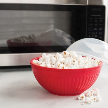 Bowl with microwaved popcorn in front of microwave