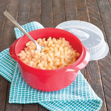 Microwaved macaroni and cheese in multi boiler with spoon, lid on side