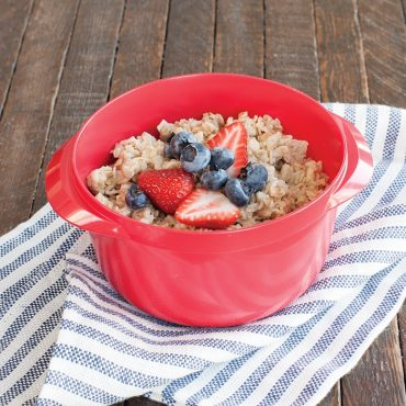 red multi boiler with cooked oatmeal and fresh fruit garnish