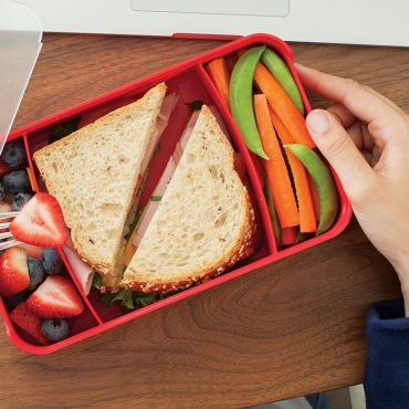 Bento Box container compartments with fresh fruit, sandwich, carrots and snap peas on desk