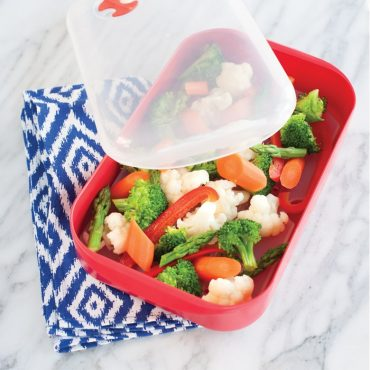 Steamer with microwaved mixed vegetables, lid on side