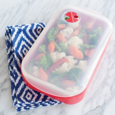 Steamer container with steamed mixed vegetables, lid on container
