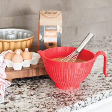 Cake batter in bowl, whisk; eggs; cast Elegant Bundt® cake pan, cinnamon spice cake mix box on counter