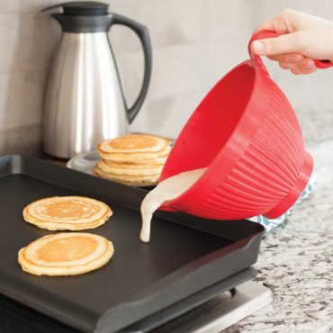 Pancake batter pouring out pancake batter onto griddle, pancakes on plate, coffee craft in background