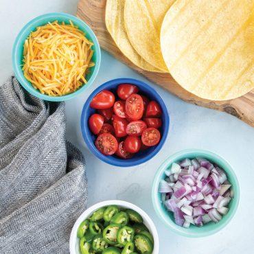 Taco fixings in 4 mini prep bowls, tortillas on side