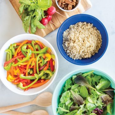 3 bowls with salad ingredients, wooden spoon, vegetables on cutting board