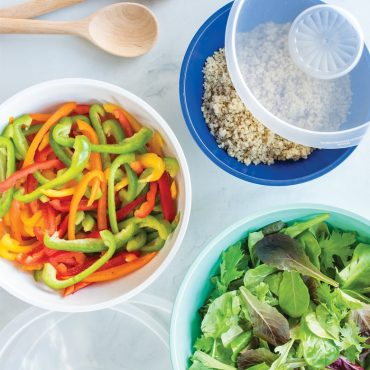 3 bowls with salad ingredients, lids, wooden spoon