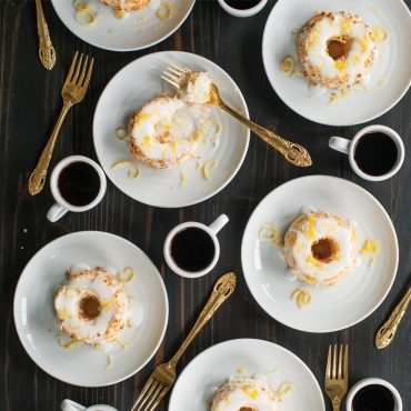baked angel food cakes on plates with glaze and lemon zest garnish, forks and coffee in cups