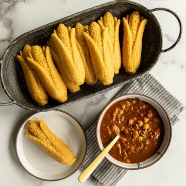 Cup of chili with baked cornbread on a plate, platter of cornbread cakes in a platter.