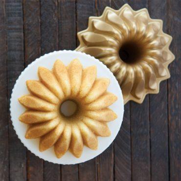 Top view baked vanilla Lotus Bundt cake on plate, Lotus pan beside cake