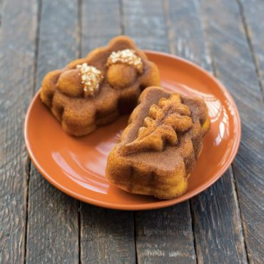Two baked spice mini loaves on plate with chopped nut garnish