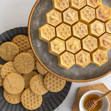 Baked honeycomb cake with bee cookie stamps on plate with honey jar with dipper on surface