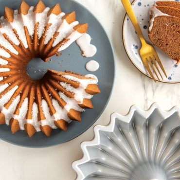 Baked Brilliance spice cake with white glaze on serving plate, piece cut from cake on plate, cake pan on the side