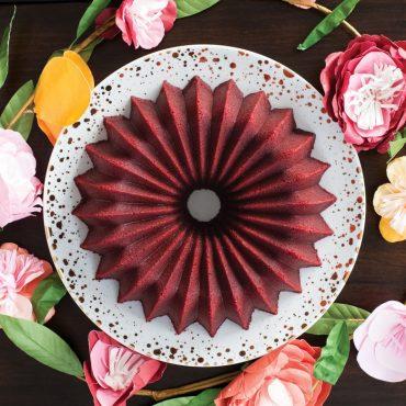 Baked red velvet cake on serving plate, fresh flowers around serving plate