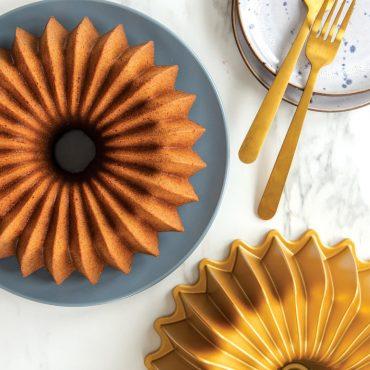 Baked Brilliance spice cake on serving plate with cake pan on the side