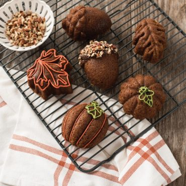 Six baked pumpkin cakelets with various piped colored frosting designs on cooling rack, one with chopped nuts