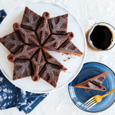 Chocolate snowflake cake on platter with a cut piece on a plate, cup of coffee