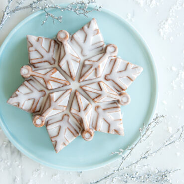 Glazed snowflake cake on blue cake plate with snow decorations in background