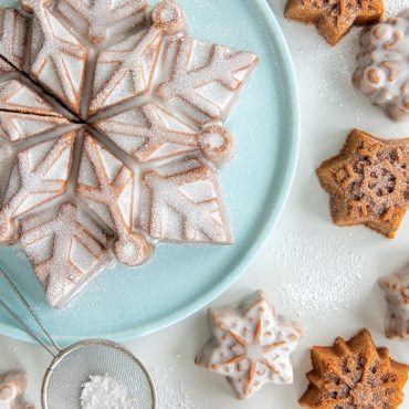 Baked and glazed snowflake cake on a blue platter, snowflake cakelets on the surface, dusted with powdered sugar