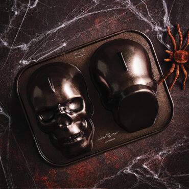 Skull Cake Pan on dark surface with webs around it
