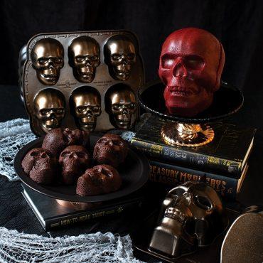 Baked red velvet skull cake on cake stand, cake pan on the side, baked chocolate skull cakelets on serving plate, skull cakelet pan on the side