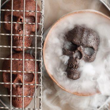 Single chocolate skull cake in bowl with smoke surrounding cake