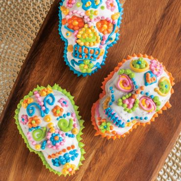 Piped bright frosting on skull cakelets