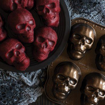 Baked red velvet skull cakelets on plate, pan on the side