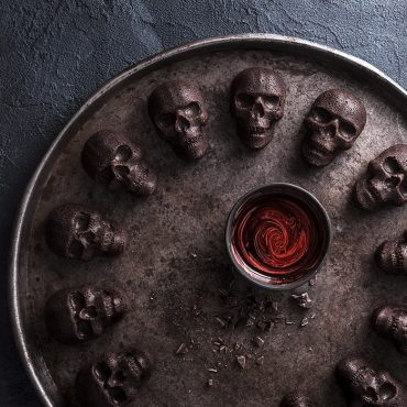 Dark chocolate skull cakelets on large circular platter, chocolate and red swirled glaze in the middle