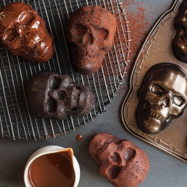 Baked chocolate skull cakeletes on cooling rack, chocolate glaze and pan in background