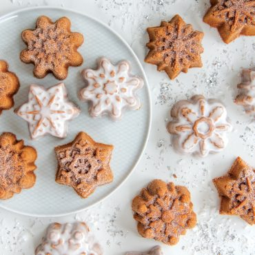 Baked snowflake cakelets on plate and surface, some dusted with powdered sugar and some glazed.