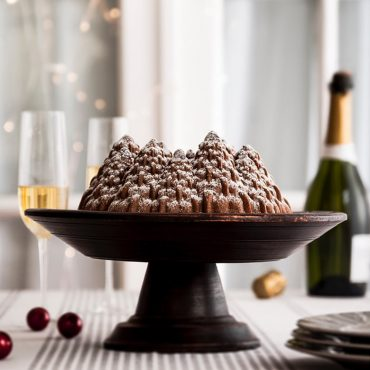 Baked spice Pine Forrest Bundt cake dusted with powdered sugar on cake stand