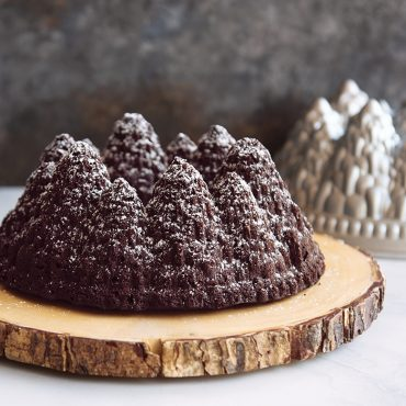 Close up Chocolate Gingerbread Pine Forest Bundt Cake on wooden plate, pan in background, dusted with powdered sugar