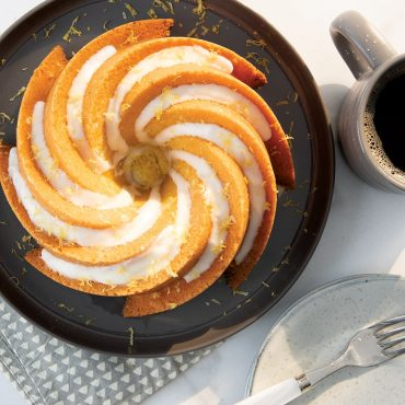 Lemon Heritage 6 Cup Bundt cake with glaze and orange shavings on plate with coffee