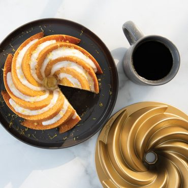 Lemon Heritage 6 Cup Bundt cake with glaze and orange shavings on plate with coffee and pan in background