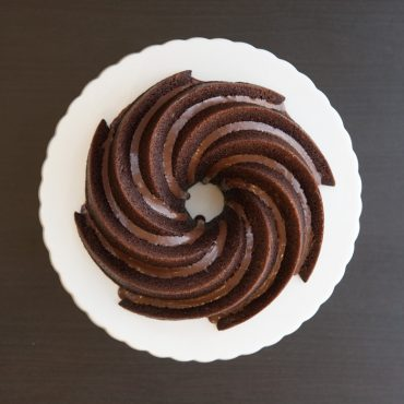 Top view of baked chocolate cake with chocolate glaze in grooves