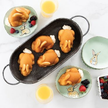 Breakfast scene with baked bunny cakes in basket, two plates with fruit