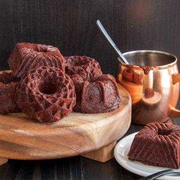 Chocolate Geo Bundt cakes on wood tray, mug with glaze in background