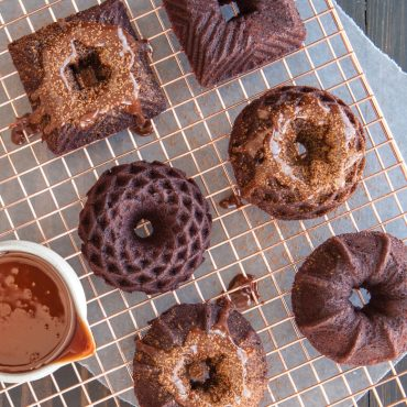Baked chocolate cakes with chocolate glaze , cocoa powder on cooling rack, pitcher of chocolate glaze next to cakes