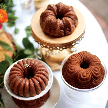 Three baked spice Bundt Quartet cakes on dessert table display with flowers