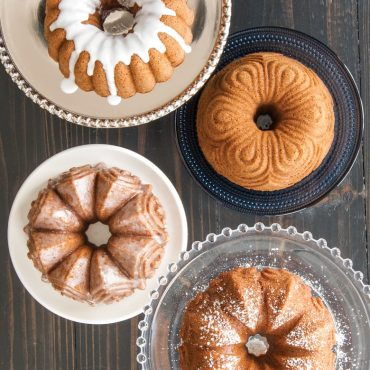 Top view of baked vanilla Bundt cakes, all four designs, one white glaze, one plain, one dusted with powdered sugar, one with glaze on whole cake