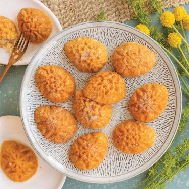 Baked cakes using Ornamental Egg Cakelet Pan on plates on blue background with flowers