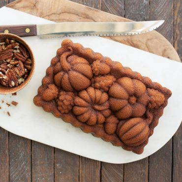 Baked pumpkin loaf cake on serving plate with bowl of pecans overhead