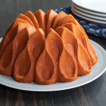 Angled view baked vanilla Crown Bundrt cake on serving plate plain