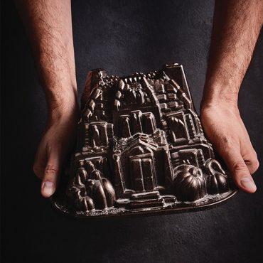 Hands holding Haunted Manor Bundt with dark background