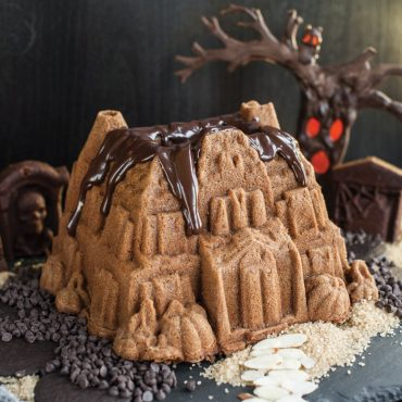 Baked Haunted Manor spice cake with thick chocolate glaze on roof, on counter with mini chocolate chips around house, slivered almonds and chopped almonds for walkway, tree with red lit up face in background