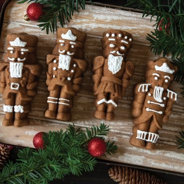 Baked spice Nutcracker cakelets with white piped frosting details, pine decorations