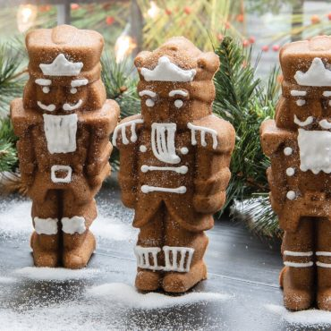 """Baked spice Nutcracker cakelets standing on counter, close up to show details, piped white frosting details, granulated sugar """"snow""""around feet, pine in background"""