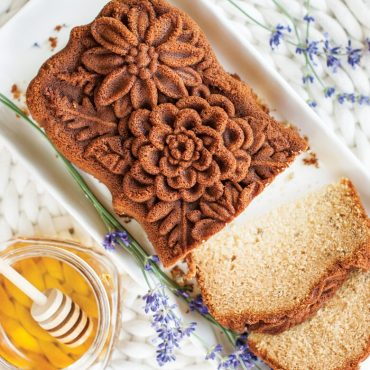 Top view baked wildflower loaf cake on serving plate, sliced, honey in jar with dipper